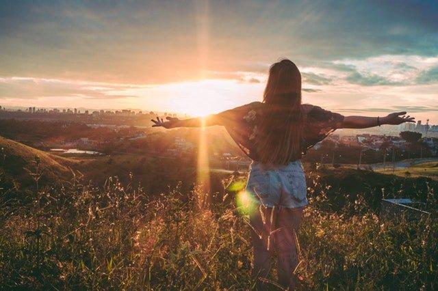 mulher em um campo no por do sol de costas com os braços abertos