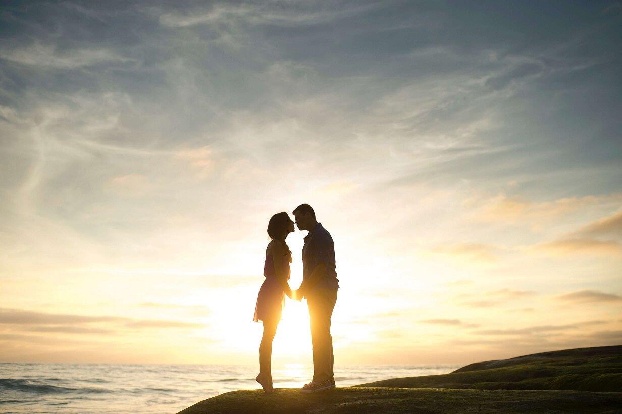 casal se beija com a silhueta contra o pôr do sol