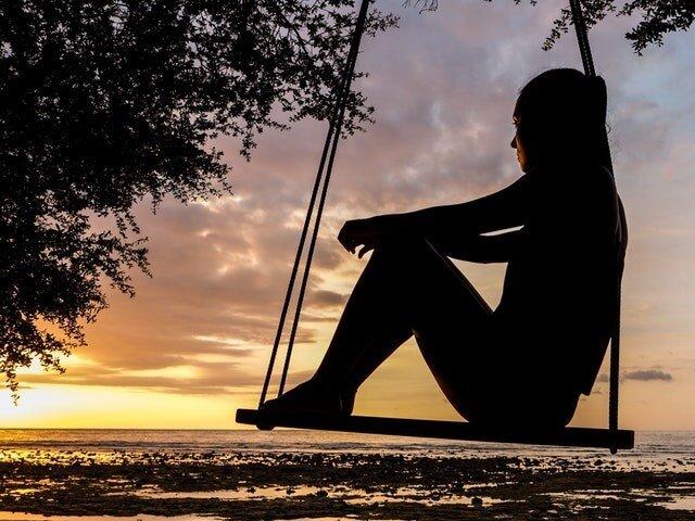 moça observa por do sol em balanço com céu livre de poluição atmosferica