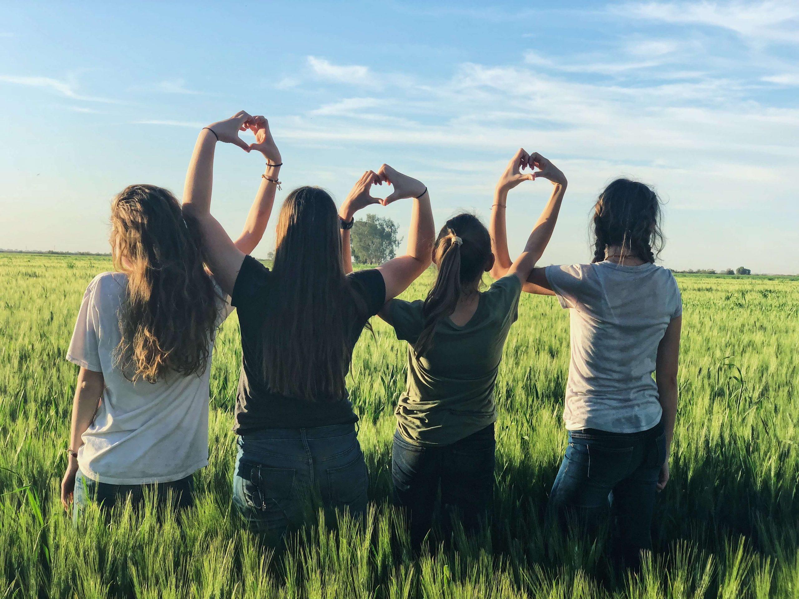 mulheres de costas com braços entrelaçados em forma de coração