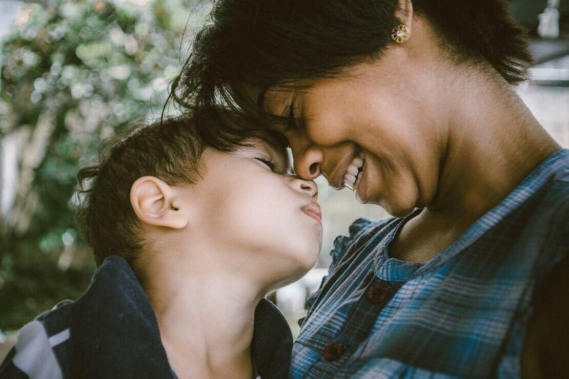 mãe e filho em momento de afeto com as cabeças coladas, em imagem para ilustrar matéria de homenagem para mãe